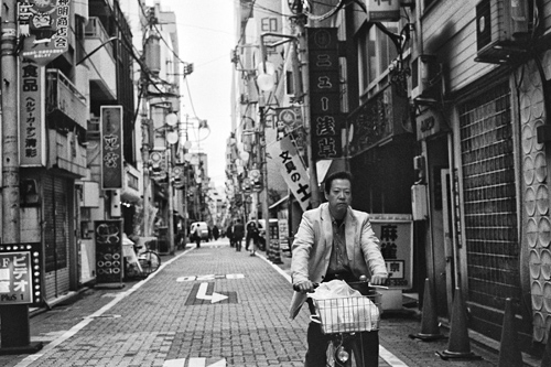 Man commuting on bicycle in Tokyo, Japan.